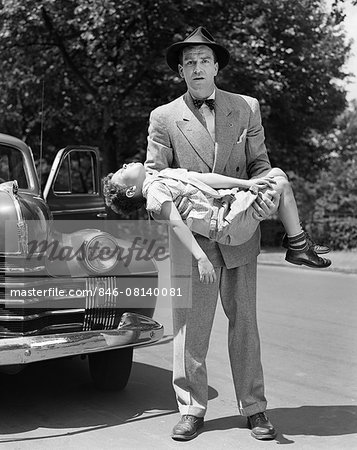 1950s DISTRAUGHT MAN LOOKING AT CAMERA CARRYING UNCONSCIOUS AND INJURED CHILD THAT WAS HIT BY A CAR Stock Photo - Rights-Managed, Image code: 846-08140081