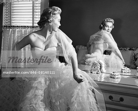 1950s BLONDE IN STRAPLESS GOWN WITH CRINOLINES TURNING TO LOOK AT BACK VIEW OF SELF IN MIRROR Stock Photo - Rights-Managed, Image code: 846-08140111