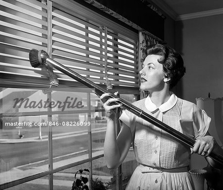 1950s WOMAN VACUUMING VENETIAN BLINDS ON WINDOW LOOKING OUT ONTO SUBURBAN STREET Stock Photo - Rights-Managed, Image code: 846-08226099