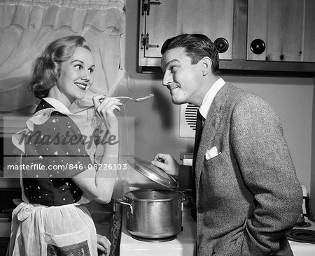 1950s SMILING HOUSEWIFE AT STOVE GIVING HAPPY HUSBAND TASTE OF HER COOKING