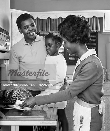 1960s AFRICAN AMERICAN FAMILY IN KITCHEN FATHER AND DAUGHTER WATCHING MOTHER REMOVE ROAST TURKEY FROM OVEN Stock Photo - Rights-Managed, Image code: 846-08226105