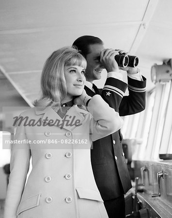 1960s MAN OFFICER IN UNIFORM USING BINOCULARS AND STYLISH BLOND WOMAN STANDING TOGETHER ON BRIDGE OF A CRUISE SHIP Stock Photo - Rights-Managed, Image code: 846-08226162