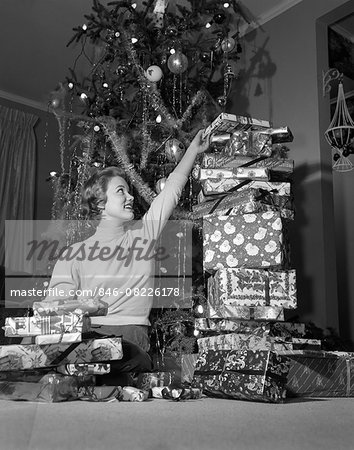 1950s SMILING YOUNG WOMAN SITTING UNDER CHRISTMAS TREE STACKING TALL PILE OF GIFT WRAPPED PRESENTS Stock Photo - Rights-Managed, Image code: 846-08226178