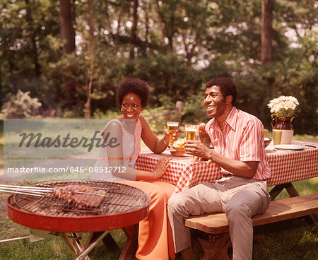 1970s SMILING AFRICAN AMERICAN COUPLE MAN WOMAN DRINKING BEER AT BACKYARD BARBECUE Stock Photo - Rights-Managed, Image code: 846-08512712