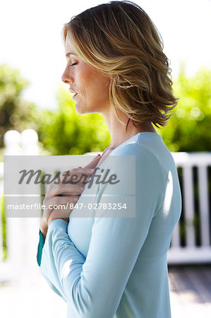 Beautiful mature woman performing yoga at the beachhouse.