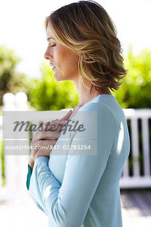 Beautiful mature woman performing yoga at the beachhouse.
