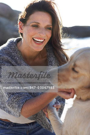 Beautiful lady playing with dog on the beach Stock Photo - Rights-Managed, Image code: 847-03067983