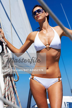 Girl in white bikini standing on sailing boat Stock Photo - Rights-Managed, Image code: 847-03652374