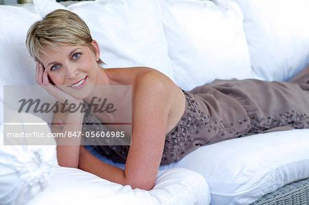 Elegant, mature woman lying on white settee Stock Photo - Rights-Managed, Image code: 847-05606985