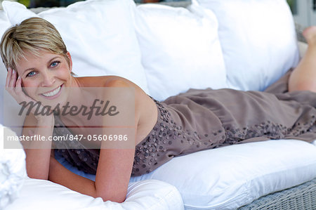 Elegant, mature woman lying on white settee Stock Photo - Rights-Managed, Image code: 847-05606986