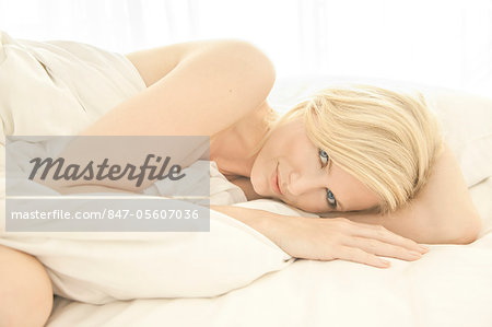 Blonde woman lying on a bed wrapped in a sheet Stock Photo - Rights-Managed, Image code: 847-05607036