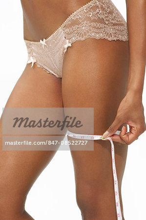 Afro-caribbean woman measuring her thigh with tape Stock Photo - Rights-Managed, Image code: 847-08522727