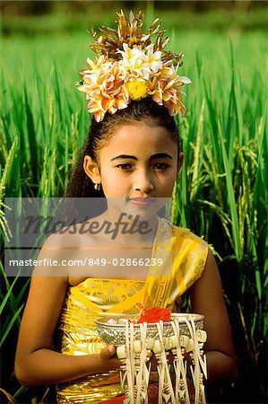 Indonesia, Bali, Young Balinese dancer in costume with offerings in rice paddy. Stock Photo - Rights-Managed, Image code: 849-02866239