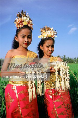 Indonesia, Bali, Young Balinese dancers in costume with offerings in rice paddy. Stock Photo - Rights-Managed, Image code: 849-02866240