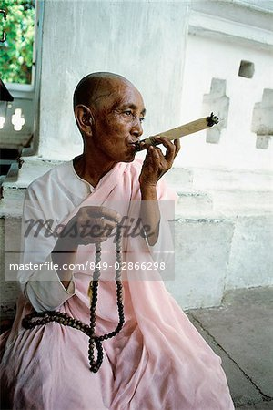 Myanmar, Mandalay area, Nun smoking cigar while holding prayer beads Stock Photo - Rights-Managed, Image code: 849-02866298