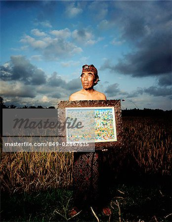 Indonesia, Bali, Ubud, Balinese artist holding painting in rice field. Stock Photo - Rights-Managed, Image code: 849-02867615