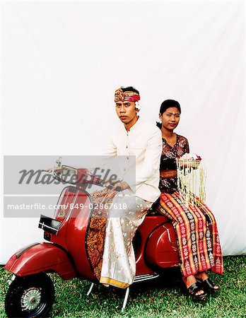 Indonesia, Bali, Ubud, Balinese wedding couple in ceremonial dress, sitting on motor scooter, woman carrying offering. Stock Photo - Rights-Managed, Image code: 849-02867618