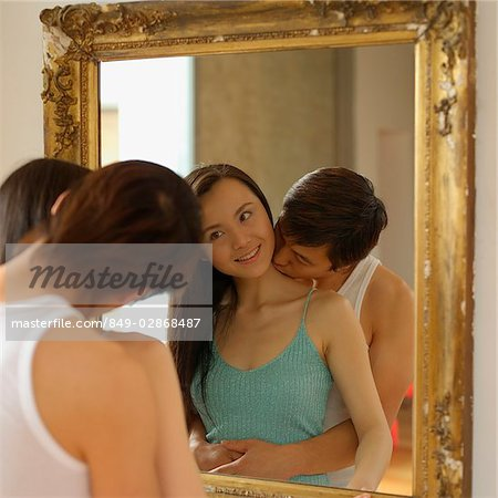 Woman looking at mirror, man kissing her neck Stock Photo - Rights-Managed, Image code: 849-02868487