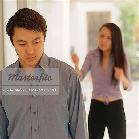 Man looking down, woman behind him gesturing Stock Photo - Rights-Managed, Image code: 849-02868493