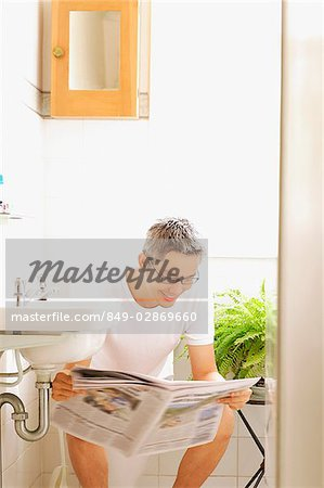 Man on toilet, reading newspaper Stock Photo - Rights-Managed, Image code: 849-02869660