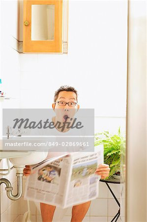Man on toilet, holding newspaper, mouth open Stock Photo - Rights-Managed, Image code: 849-02869661