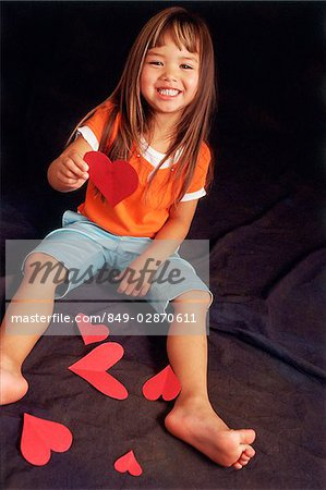 Young girl holding paper hearts, looking at camera Stock Photo - Rights-Managed, Image code: 849-02870611