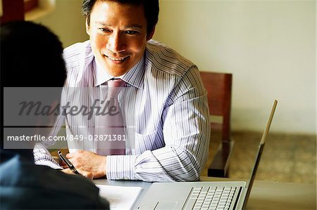 Businessmen talking, laptop open next to them Stock Photo - Rights-Managed, Image code: 849-02871381