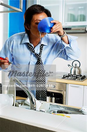 Man in kitchen, drinking from bowl Stock Photo - Rights-Managed, Image code: 849-02871464