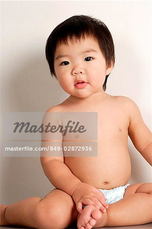 Toddler in diapers, sitting and looking at camera