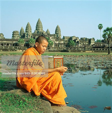 Cambodia, Sien Reap, Province, Angkor Wat, Buddhist monk reading Buddhist manuscript in front of temple Stock Photo - Rights-Managed, Image code: 849-02874985