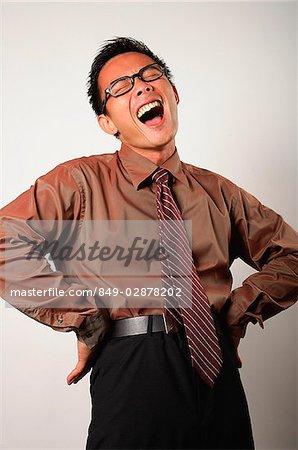 Nerdy businessman with hands on hips, laughing Stock Photo - Premium
