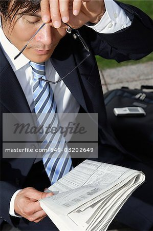 Businessman holding glasses and paper Stock Photo - Rights-Managed, Image code: 849-03202649