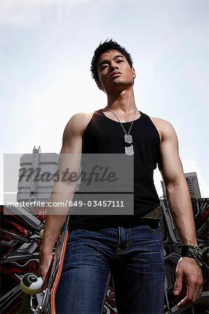Young man holding skateboard and looking tough Stock Photo - Rights-Managed, Image code: 849-03457111