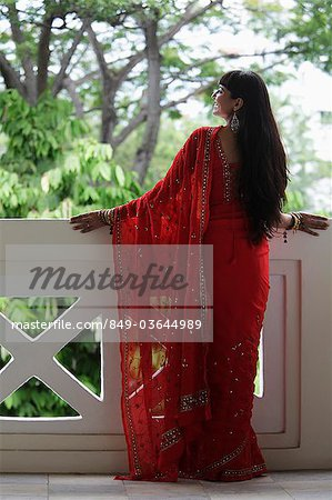 Back shot of Indian woman wearing a red sari looking over balcony. Stock Photo - Rights-Managed, Image code: 849-03644989
