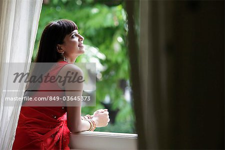 Indian woman looking out window, smiling Stock Photo - Rights-Managed, Image code: 849-03645373