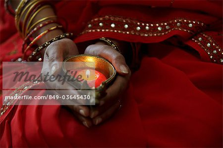 Close up of woman wearing red sari and holding lit candle Stock Photo - Rights-Managed, Image code: 849-03645430