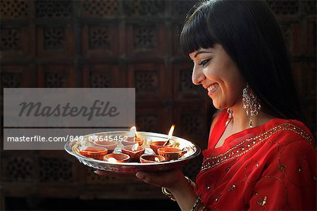 Profile shot of Indian woman holding a tray of lit oil lamps Stock Photo - Rights-Managed, Image code: 849-03645452