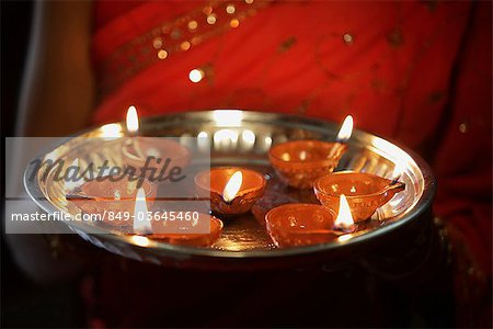 Cropped shot of woman holding a silver tray of oil lamps. Stock Photo - Rights-Managed, Image code: 849-03645460