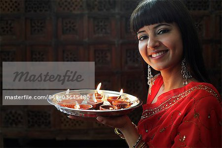 Indian woman holding tray of lit oil lamps Stock Photo - Rights-Managed, Image code: 849-03645480