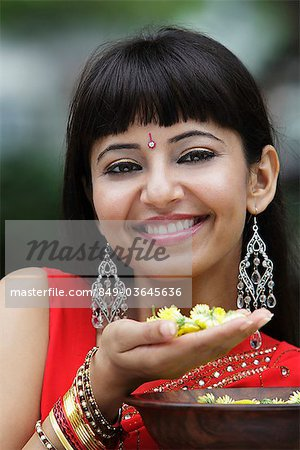 Head shot of Indian woman smiling and holding flowers Stock Photo - Rights-Managed, Image code: 849-03645636
