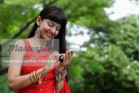 Indian woman texting on phone, outdoors Stock Photo - Rights-Managed, Image code: 849-03645660