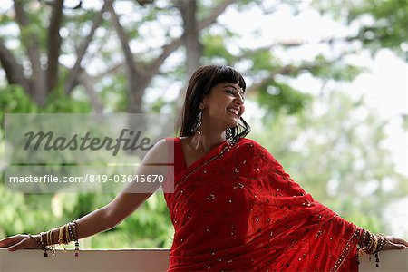Indian woman wearing red sari leaning on balcony, smiling Stock Photo - Rights-Managed, Image code: 849-03645670