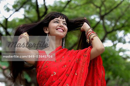 Indian woman wearing red sari smiling with hands in hair Stock Photo - Rights-Managed, Image code: 849-03645706