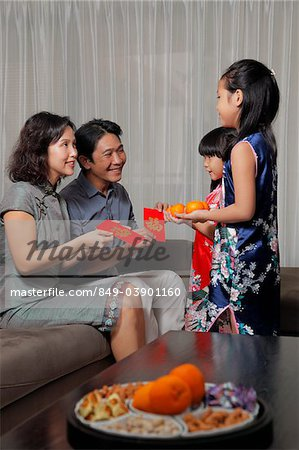 Chinese parents giving red envelopes (Hong Bao) to daughters during Chinese New Year Stock Photo - Rights-Managed, Image code: 849-03901160