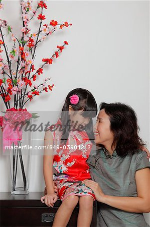 Chinese mother and daughter wearing Cheongsams looking at eachother Stock Photo - Rights-Managed, Image code: 849-03901212