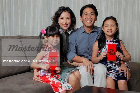 Chinese family sitting together with daughters holding red envelopes (Hong Bao) Stock Photo - Rights-Managed, Image code: 849-03901235