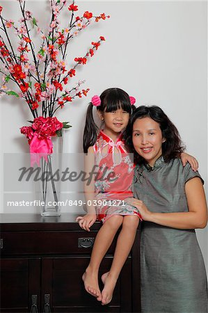 Chinese mother and daughter wearing Cheongsams sitting near flowers Stock Photo - Rights-Managed, Image code: 849-03901271