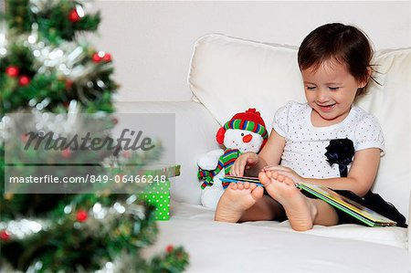 Young girl reading a book, Christmas tree in foreground Stock Photo - Rights-Managed, Image code: 849-06466248