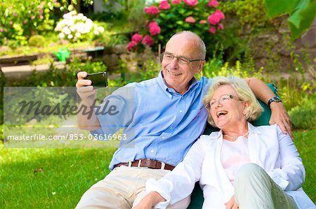 Happy senior couple with smartphone in garden Stock Photo - Rights-Managed, Image code: 853-03616963