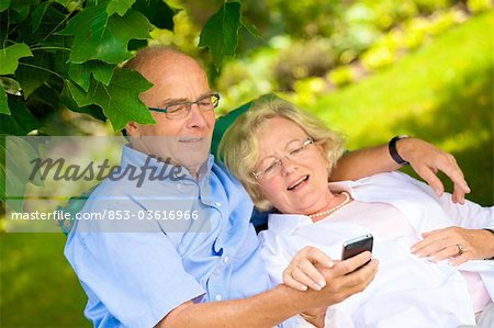 Happy senior couple with smartphone in garden Stock Photo - Rights-Managed, Image code: 853-03616966